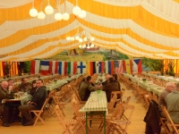 Wnętrze wielkiego namiotu z widokiem na ścianę pokrytą flagami uczestników